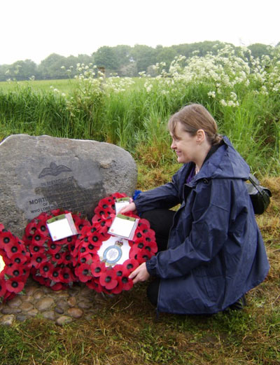 Hilary Mortimer, a descendant of Sgt Ellis laying a Poppy wreath on the memorial